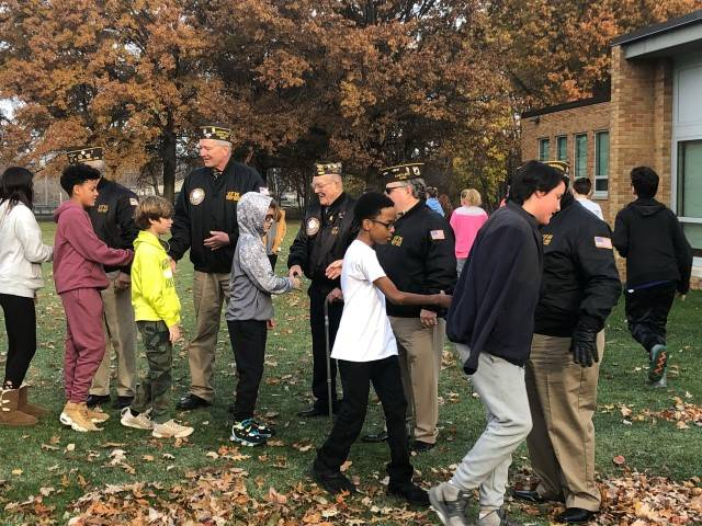 Students walk by veterans and thank them for their service.
